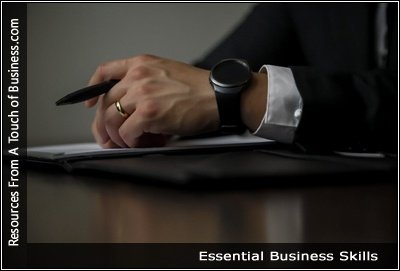 Image of a well dressed man holding a pen and siting a desk